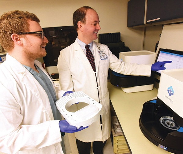 Dr. Eric Rosenbaum (right) and pathology resident Jonathon Gralewski, DO, in the University of Arkansas for Medical Sciences clinical microbiology lab with the Accelerate Pheno. All reactions and analyses are automated, Dr. Rosenbaum says, and bench experience is not needed to run the test 24 hours per day. Photo credit: Johnpaul Jones, UAMS